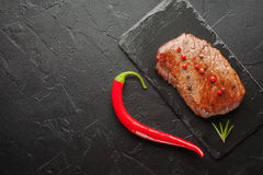 Зажаренный стейк с chili на черном камне Стоковое Изображение