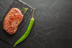 Зажаренный стейк с chili на черном камне Стоковые Изображения