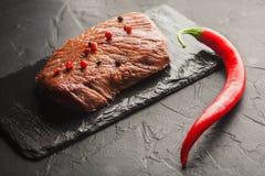 Зажаренный стейк с chili на черном камне Стоковая Фотография