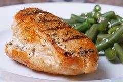 Зажаренный стейк цыпленка на белой плите с зелеными фасолями Стоковые Фотографии RF