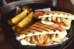 Зажаренный сэндвич с курицей с фраями служил на плите Стоковая Фотография RF