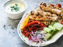 Зажаренный цыпленок на протыкальниках металла со свежими овощами на пите и греческом соусе в шаре на серой предпосылке греческо стоковое фото rf