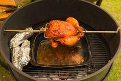 Зажаренный цыпленок, bbq, над открытыми пламенами в барбекю Стоковая Фотография RF