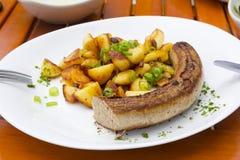 Зажаренный bratwurst с зажаренными картошками на плите Стоковая Фотография RF