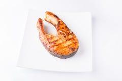 Зажаренный salmon стейк изолированный на белой плите стоковое фото rf