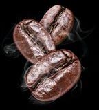 3 зажаренных в духовке кофейного зерна на черной предпосылке Стоковая Фотография