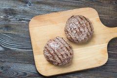 2 зажаренных пирожка гамбургера на деревянной предпосылке Стоковые Фото