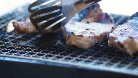 Зажарил и поворачивает мясо свинины на гриле сток-видео