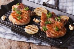 2 зажарили стейк свинины в конце-вверх гриля лотка горизонтально Стоковые Фотографии RF