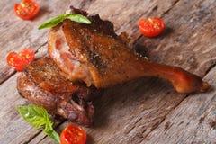 2 зажарили утиные ножки и базилик, крупный план томатов вишни на таблице Стоковое Изображение