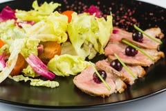 Зажженное мясо с салатом На черной плите Стоковые Изображения RF