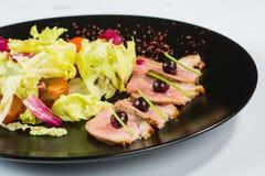Зажженное мясо с салатом На черной плите Стоковая Фотография RF