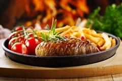 Зажженное мясо с французскими фраями Стоковая Фотография
