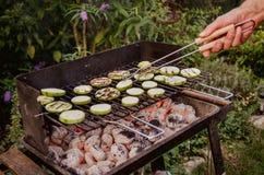 зажженные овощи Человек поворачивает овощи на гриле для избежания поцарапать Стоковое Изображение RF