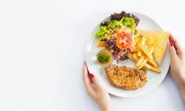 Зажженные стейки, испеченные картошки и овощи на белой плите дальше Стоковые Изображения