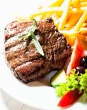 Зажженный стейк говядины с французскими fries Стоковые Фото