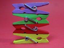 Зажимки для белья 4 других цветов на розовой предпосылке Стоковое Изображение RF