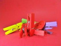 Зажимки для белья других цветов на шестках предпосылки пинка на верхней части Стоковые Фото