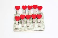 Зажимки для белья с сердцами на куске бумаги Стоковые Фото