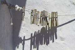 Зажимки для белья на веревочке на белизне стены предпосылки Стоковая Фотография