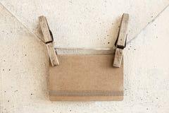 Зажимки для белья проводя приветствовать карточку пустого ремесла бумажную Стоковое Изображение