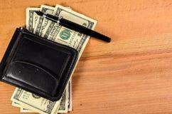 Зажим денег и 100 долларов банкнот на деревянном столе Стоковая Фотография