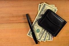 Зажим денег и 100 долларов банкнот на деревянном столе Стоковое Изображение RF