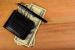Зажим денег и 100 долларов банкнот на деревянном столе Стоковые Фото