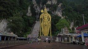 Зажим замедленного движения голубей летания на статуе переднего плана и золота Murugan против стены утеса, Gombak, Selangor, Мала видеоматериал