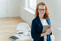 Зажиточный женский руководитель работая команды держит цифровой прибор планшета, начинает идеи дела, имеет зубастую улыбку, красн стоковое фото rf