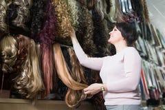 Заинтересованная женщина выбирая расширение волос в салон Стоковая Фотография