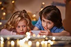 Заинтересованные включенные дети используя smartphone совместно Стоковое Изображение