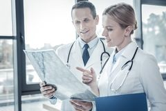 Заинтересованные ответственные доктора рассматривая рентгеновский снимок просматривают фокусировать на ем Стоковая Фотография