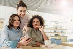 Заинтересованные усмехаясь девушки в кафе Стоковые Изображения RF