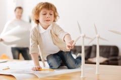 Заинтересованный в ребенке силы энергии касаясь модели одной турбины Стоковые Фото