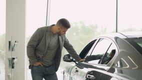 Заинтересованный клиент проверяет красивый автомобиль в выставочном зале мотора, смотрит автомобиль и касается ему Фокус на сияющ видеоматериал