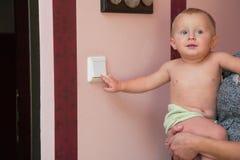 Заинтересованный мальчик поворачивая выключатель Стоковое фото RF