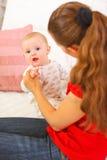 Заинтересованный младенец играя с матями на кресле Стоковые Изображения