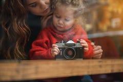 Заинтересованный ребенок принимая фото улицы from inside Стоковые Изображения