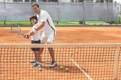 Заинтересованный ребенок уча сыграть теннис тренером Стоковое Изображение RF