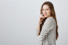 Заинтригованная девушка имеет что-то любознательное на разуме Портрет привлекательной обычной студентки стоя в профиле и Стоковые Фотографии RF