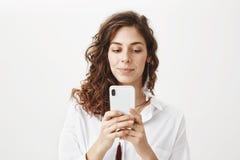 Заинтригованная и положительная чувственная кавказская женщина при вьющиеся волосы держа smartphone пока послание или играя игры стоковые фотографии rf