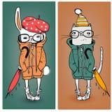 Зайцы и кот в теплых одеждах Стоковые Изображения