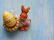 Зайцы пасхи с покрашенным яичком, диаграммой зайчика пасхи на голубой деревянной затрапезной предпосылке Стоковые Изображения