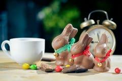 3 зайчика шоколада около ретро будильника Стоковое Фото