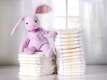 Зайчик игрушки сидя на стоге устранимых пеленок или ворсистых, стоге пеленок, изнеживает стоковые фотографии rf