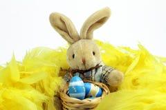 Зайчик пасхи на желтых пер и покрашенное яичко в деревянной корзине Стоковые Изображения RF