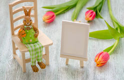 Зайчик пасхи сидя на табуретке с яичком, крася мольбертом и тюльпанами над деревянной предпосылкой Стоковая Фотография RF