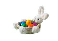Зайчик пасхи с покрашенными яичками в корзине изолированной на белой предпосылке Стоковое Изображение