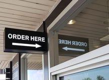 Заказ ярлыка здесь на внешней витрине магазина стоковая фотография